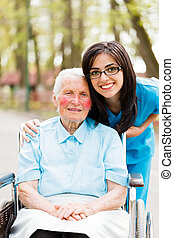 Nurse and Patient - Kind elderly lady in wheelchair with a...