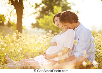 Pregnant couple - Happy and young pregnant couple hugging in...