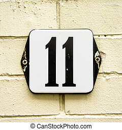 Number 11 - Enameled house number eleven on a yellowish...