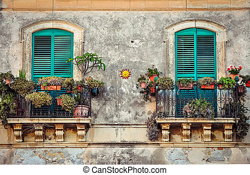 Beautiful vintage balcony with colorful flowers and doors -...