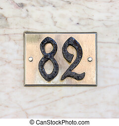 Number 82 - Wrought iron house number on a metal plate.