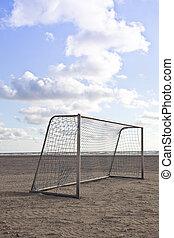 Soccer goal on beach with blue sky