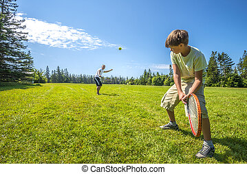 Boys playing a tennis in the park