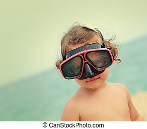 Happy child girl in diving mask smiling on beach background....