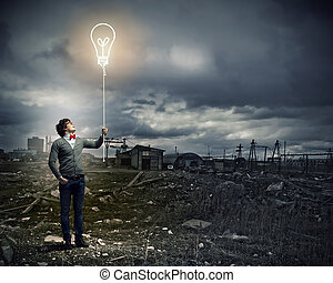 Young man holding a light at his hands against polluted and...