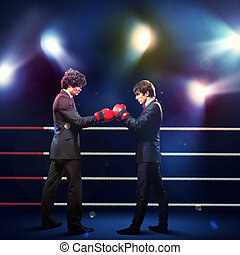 Two young businessman boxing againts dark background...