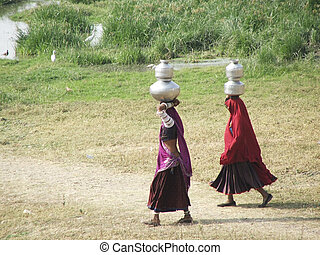 traditional indian women - two rajistani women carrying...