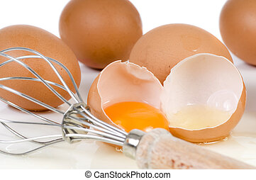 Eggs and Wisk - A broken egg and wisk ready to mix Focus on...