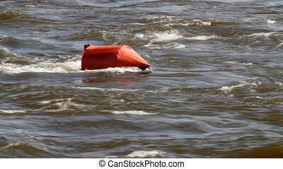 Red buoy in a river - Threshold on river Floating red buoy...