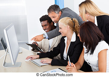 Group Of Businesspeople Looking At Computer - Businessman...