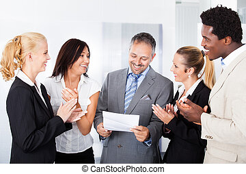 Happy Businesspeople Applauding Businessman - Happy...