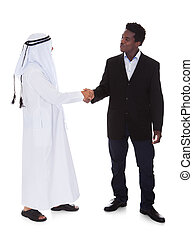 Arabic And African Man Shaking Hands