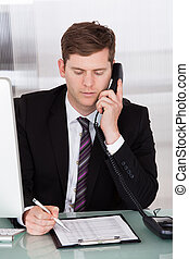 Businessman talking on telephone in office - Portrait of...