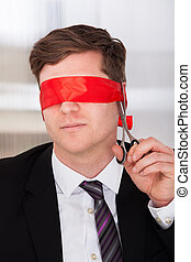 Businessman cutting his blindfold