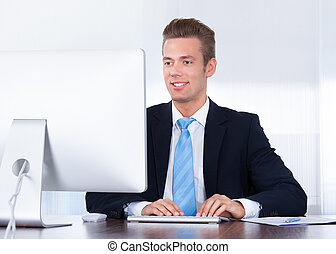 Happy Young Businessman Using Computer In Office