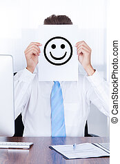 Businessman Holding Smiley Emoticon On Paper Over Face -...