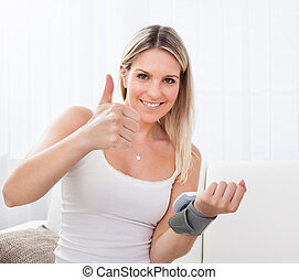Woman measuring her blood pressure - Portrait of young woman...