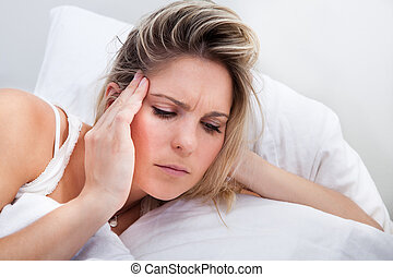 Portrait of woman with headache lying on bed