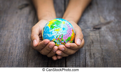 Person holding a world - A person holding a globe on wooden...