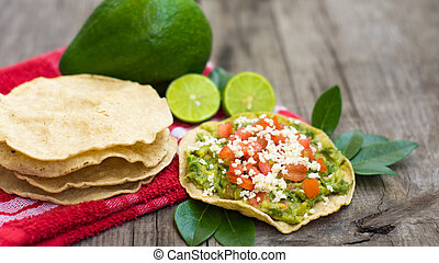Mexican Tostadas with avocado and lemon on wooden...