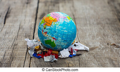 World Pollution Concept - A globe standing of a pile of...