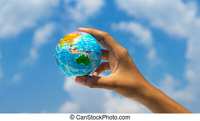 Holding a globe - A person holding a globe with clouds in...