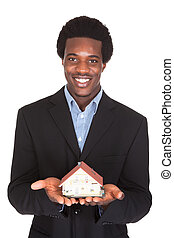 African Businessman Holding House Model - Young African...
