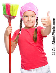 Young girl is dressed as a cleaning maid holding broom and...