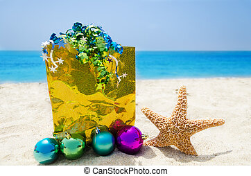 Starfish with Christmas balls and yellow gift bag on sandy beach in sunny day- holiday concept