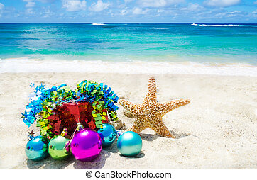 Starfish with Christmas balls and red gift box on sandy beach in sunny day- holiday concept
