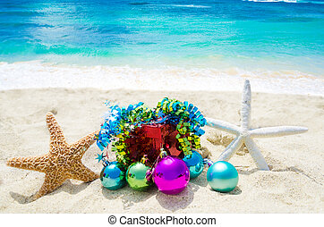 Two Starfishes with Christmas balls and gift box on sandy...