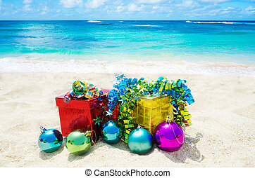 Two gift boxes with Christmas balls on sandy beach in sunny...