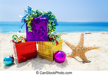 Starfish with Christmas balls and three gift boxes on sandy beach in sunny day- holiday concept