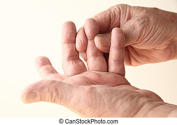 man tries to move sore finger - senior man with stiffness or...