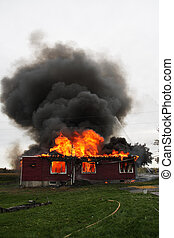 House in flame - Abandoned house in flame with firefighters...