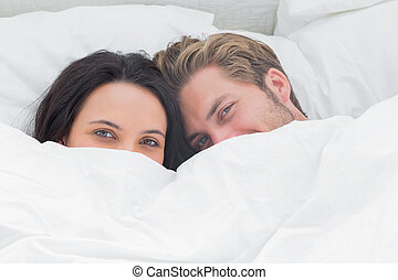 Couple hiding under the duvet in their bed