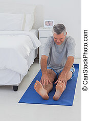 Mature man working out on mat in his bedroom