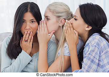 Two friends whispering secrets to surprised brunette