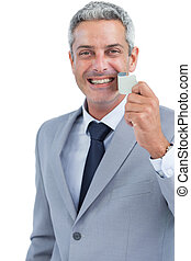 Cheerful man taking away adhesive tape from mouth on white...