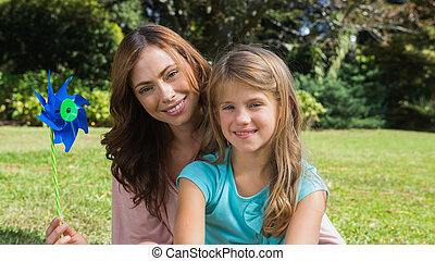 Happy mother and daughter holding pinwheel smiling at camera...
