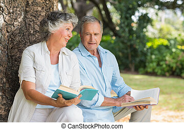 Older couple reading books together sitting on tree trunk at...