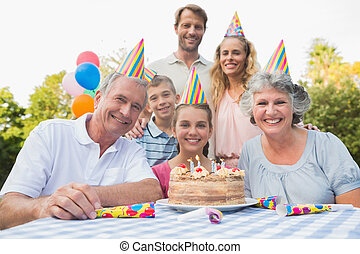 Cheerful family smiling at camera at birthday party outside...