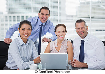 Cheerful colleagues around laptop posing in bright office