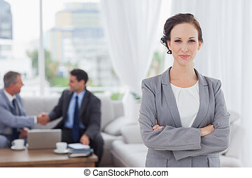 Content businesswoman posing while her colleagues are working