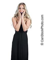 Surprised attractive blonde wearing black dress posing on...