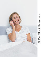 Happy blonde woman on the phone in bed smiling at camera