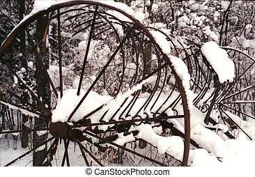 Horse drawn rake covered in snow