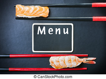 chopsticks and two sushi with salmon and shrimp with black...