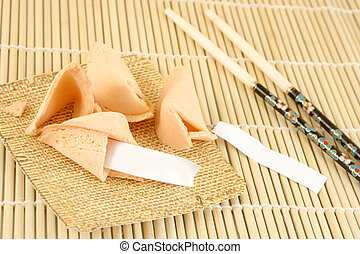 blank fortune cookies and chopsticks on a bamboo background