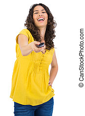 Cheerful curly haired pretty woman changing channel with...